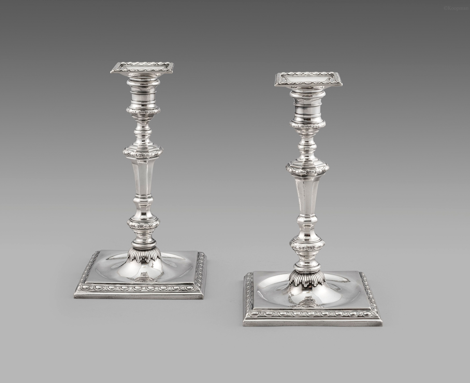A Pair of George III Square-based Neo-Classical Candlesticks