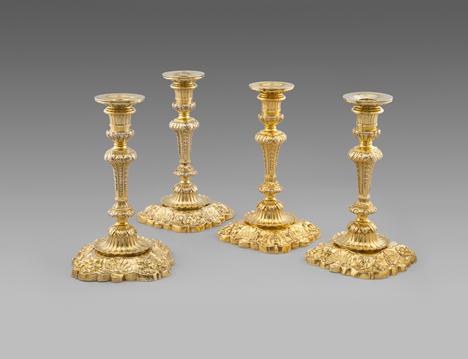 An Important Set of Four Silver-Gilt Royal Candlesticks